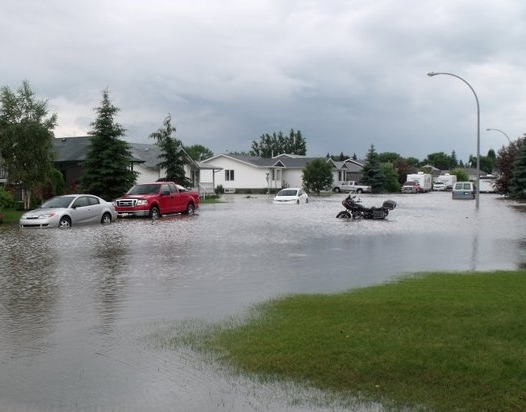 Flooded Neighborhood with Waters Completely Covering Streets and Surrounding Lawns